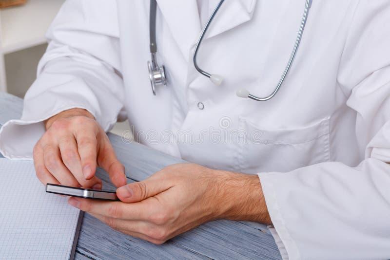 Las manos de un doctor de sexo masculino en uniforme se sientan en el escritorio y utilizan un smartphone imagen de archivo libre de regalías
