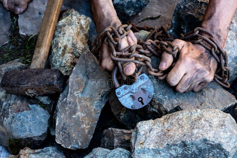 Las manos de un esclavo en un intento por lanzar El símbolo del trabajo auxiliar Manos en encadenamientos foto de archivo libre de regalías