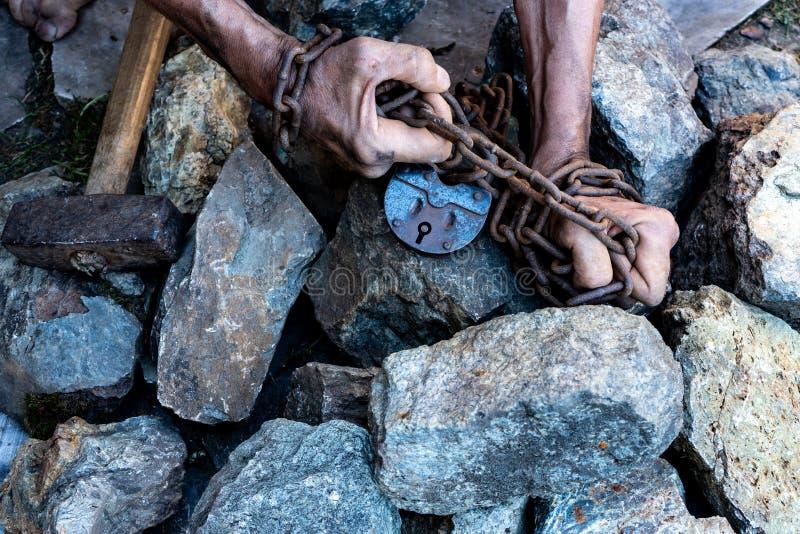Las manos de un esclavo en un intento por lanzar El símbolo del trabajo auxiliar Manos en encadenamientos imagen de archivo
