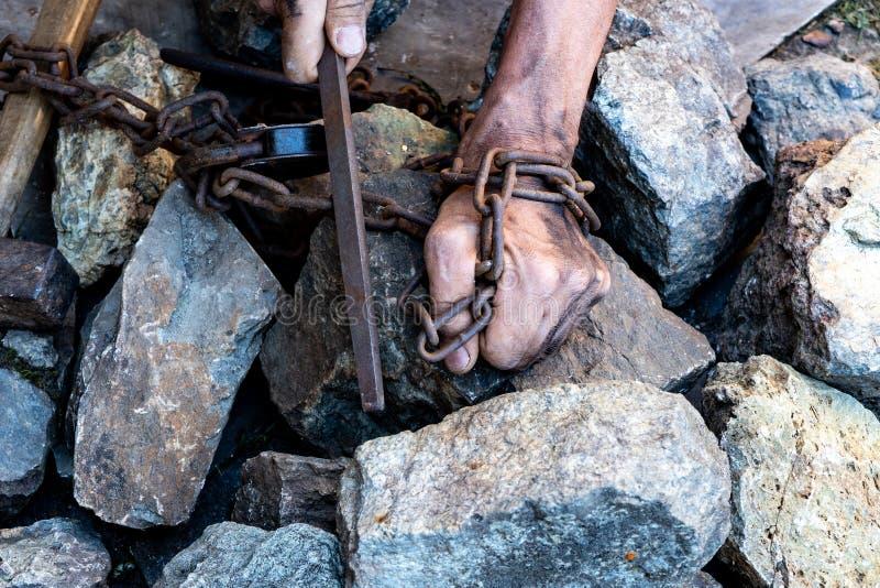 Las manos de un esclavo en un intento por lanzar El símbolo del trabajo auxiliar Manos en encadenamientos fotografía de archivo