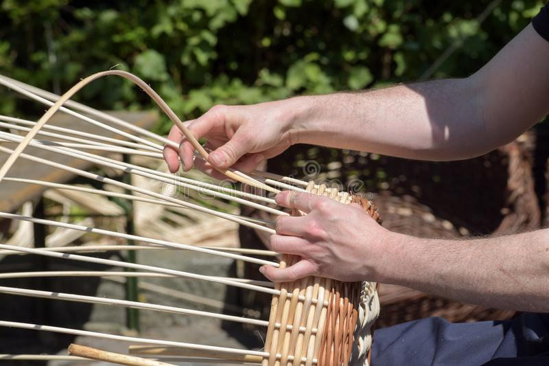 Las manos de un fabricante de cesta tejen una cesta de mimbre fotografía de archivo libre de regalías