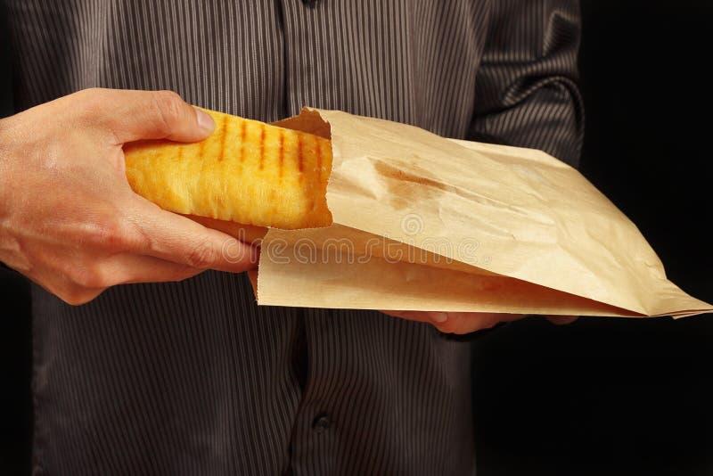 Las manos de un hombre en una camisa negra sacan un cheeseburger de un paquete en fondo negro foto de archivo