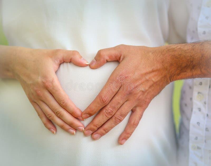 Las manos de un hombre y de una mujer se unieron a juntas en una forma del corazón sobre el vientre de una mujer embarazada imagen de archivo libre de regalías