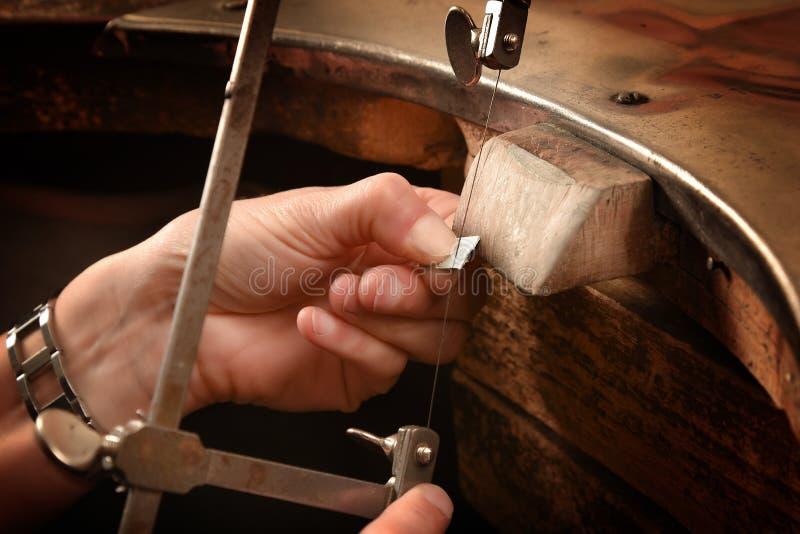 Las manos de un orfebre consideraron un pedazo de plata en el banco de trabajo con fotografía de archivo libre de regalías