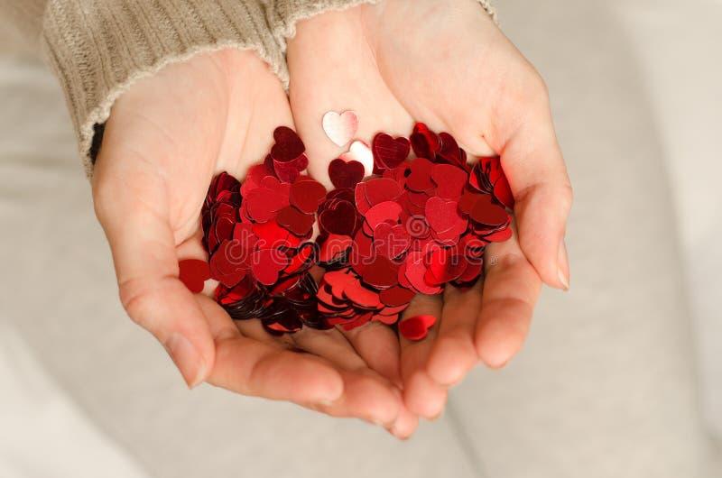 Las manos de una muchacha caucásica joven llevan a cabo pequeños corazones fotografía de archivo