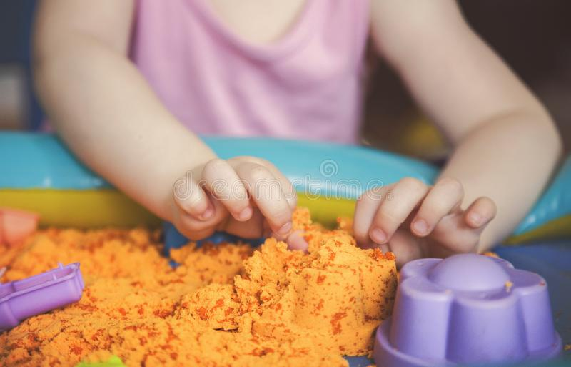 Las manos de una muchacha del niño que juega con la arena cinética E imágenes de archivo libres de regalías