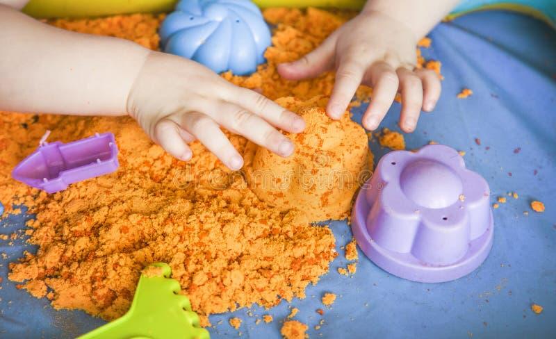 Las manos de una muchacha del niño que juega con la arena cinética E imagenes de archivo