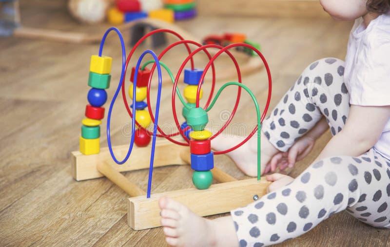 Las manos de una muchacha del niño que juega los juguetes E foto de archivo