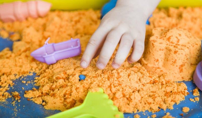 Las manos de una muchacha del ni?o que juega con la arena cin?tica E imagen de archivo libre de regalías