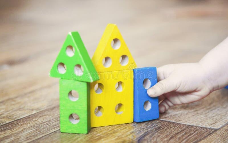 Las manos de una muchacha del ni?o que juega los juguetes E imagenes de archivo