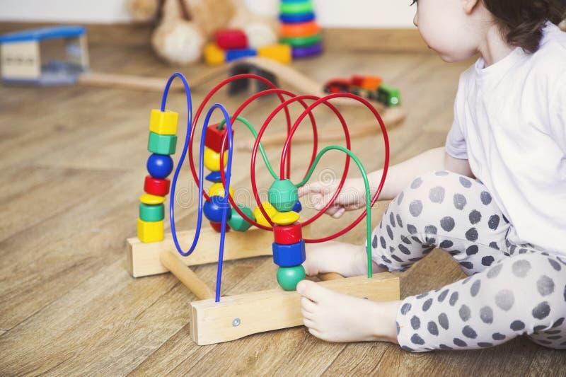Las manos de una muchacha del ni?o que juega los juguetes E foto de archivo