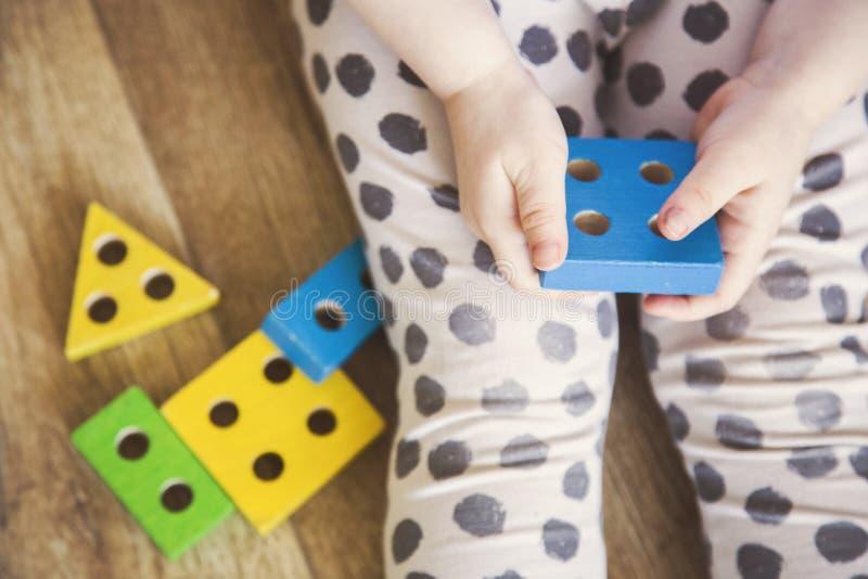 Las manos de una muchacha del ni?o que juega los juguetes E fotos de archivo