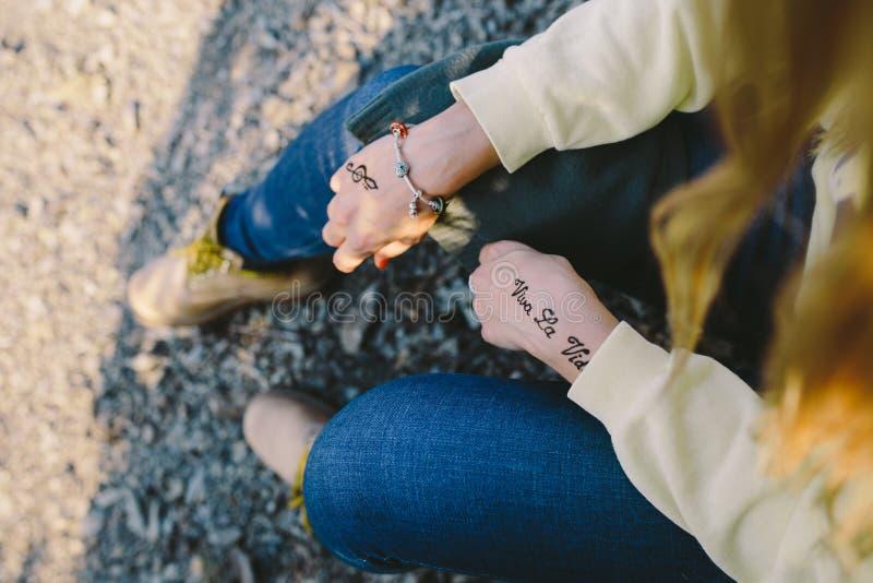 Las manos de una mujer joven con el ` y la clave de sol de Viva la Vida del ` de las inscripciones de Mehndi firman imagen de archivo libre de regalías