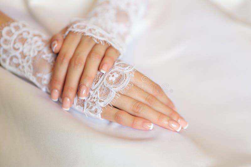 Las manos de una novia con una boda manicure imagen de archivo libre de regalías