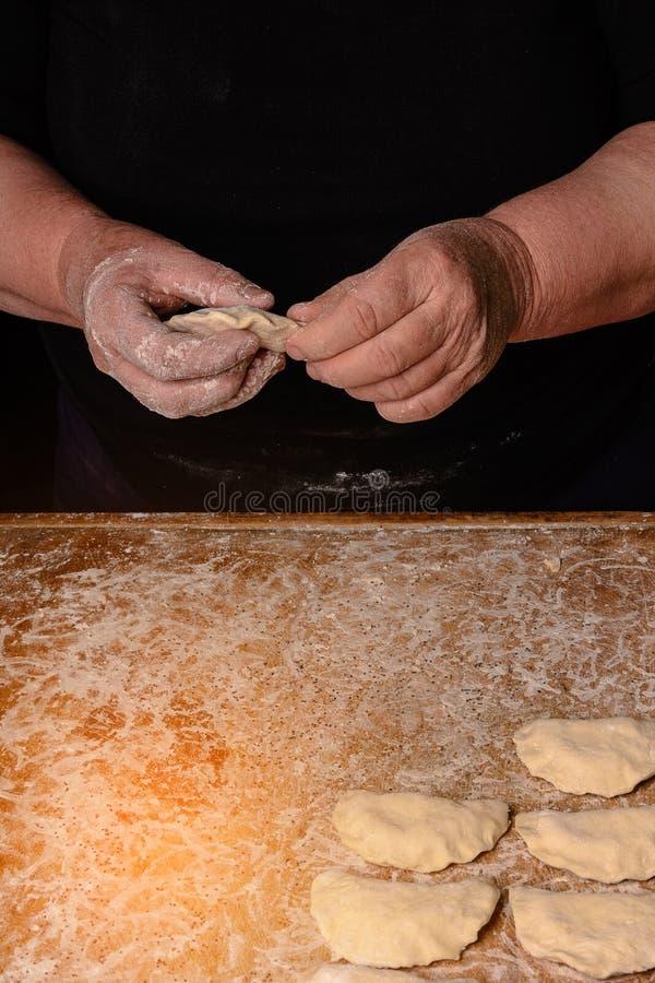 Las manos de una vieja abuela moldean vareniks en un fondo oscuro foto de archivo libre de regalías