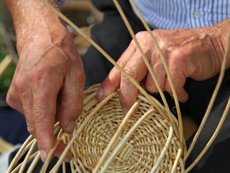 Las manos del artesano experto hacen una cesta de mimbre imagenes de archivo