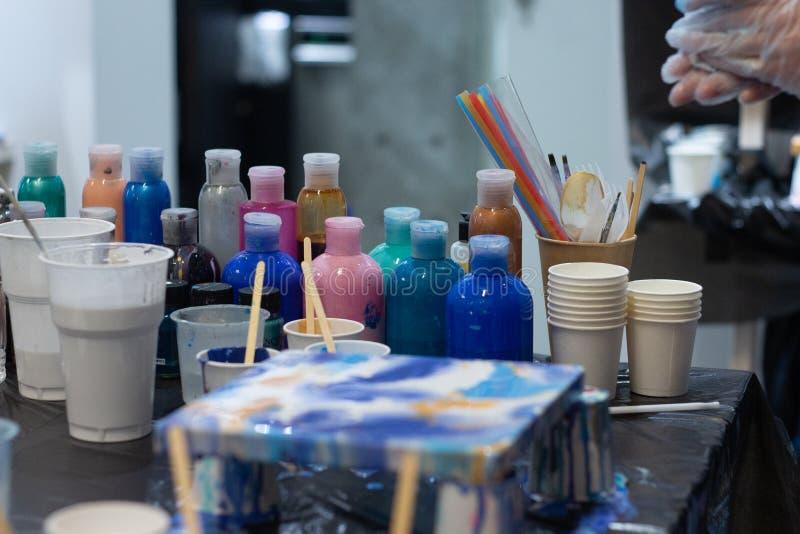 Las manos del artista están mezclando la pintura acrílica para su nuevo proyecto, diversos colores Herramientas del artista para  foto de archivo