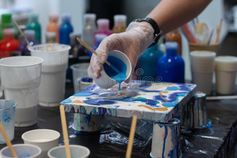 Las manos del artista están mezclando la pintura acrílica para su nuevo proyecto, diversos colores Herramientas del artista para  foto de archivo libre de regalías