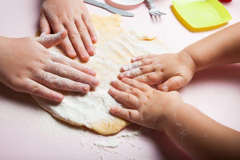 Las manos del bebé amasan la pasta, primer fotografía de archivo libre de regalías