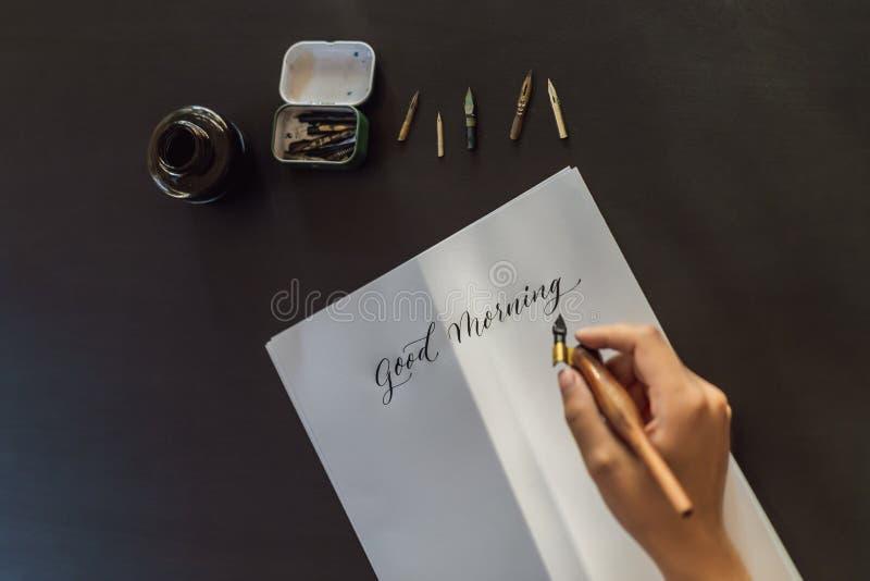Las manos del calígrafo escriben frase en el Libro Blanco Frase - buena mañana Inscripción de letras adornadas ornamentales imagenes de archivo