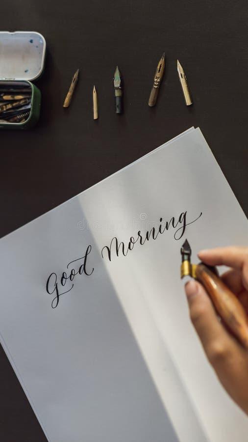 Las manos del calígrafo escriben frase en el Libro Blanco Frase - buena mañana Inscripción de letras adornadas ornamentales imagen de archivo