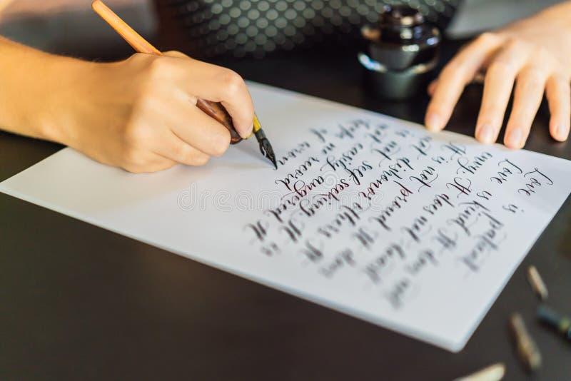 Las manos del calígrafo escriben frase en el Libro Blanco Frase de la biblia sobre el amor que inscribe letras adornadas ornament imagenes de archivo