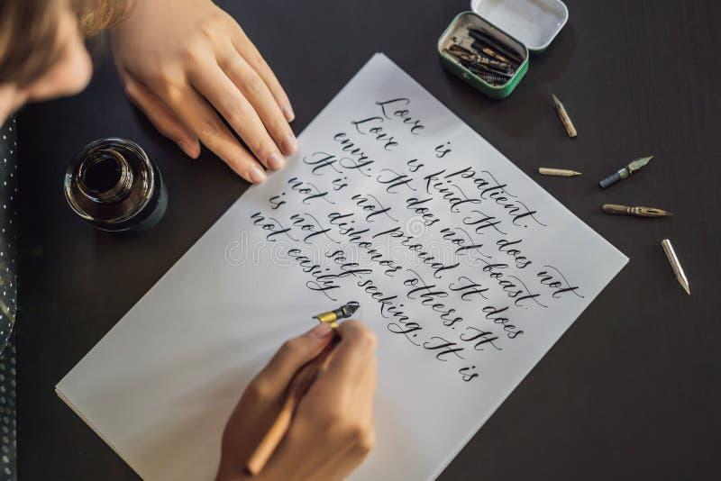 Las manos del cal?grafo escriben frase en el Libro Blanco Frase de la biblia sobre el amor que inscribe letras adornadas ornament foto de archivo libre de regalías