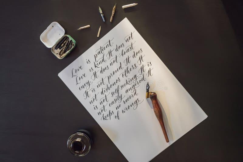 Las manos del cal?grafo escriben frase en el Libro Blanco Frase de la biblia sobre el amor que inscribe letras adornadas ornament imagen de archivo