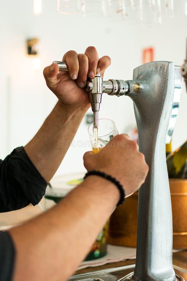 las manos del camarero en la cerveza golpean ligeramente la colada de una porci?n de la cerveza de cerveza dorada del proyecto en imágenes de archivo libres de regalías