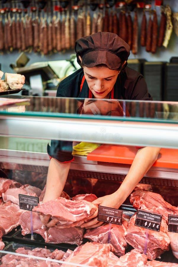 Las manos del carnicero sujetando una pieza de carne en la tienda fotografía de archivo