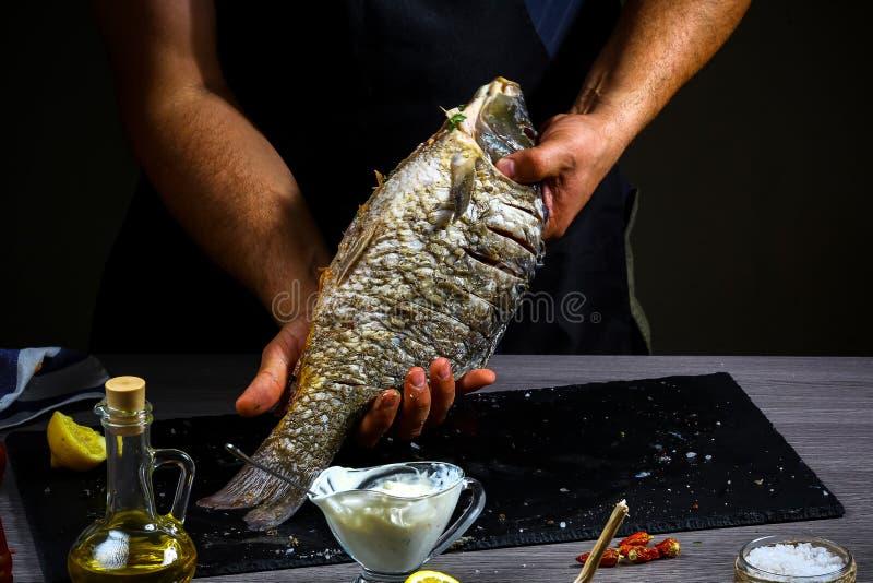 Las manos del cocinero de los pescados frescos son listas para cocer en la bandeja de la pizarra, visión superior, comida sana, c foto de archivo
