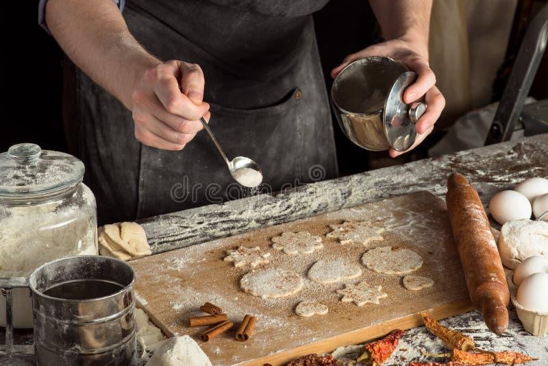 Las manos del cocinero están asperjando el azúcar fotos de archivo