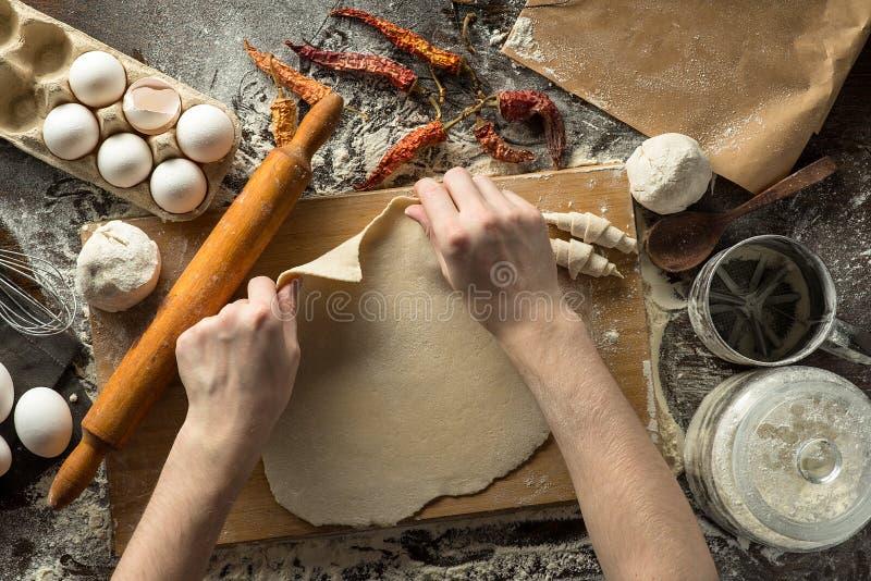 Las manos del cocinero están rodando la pasta fotografía de archivo libre de regalías