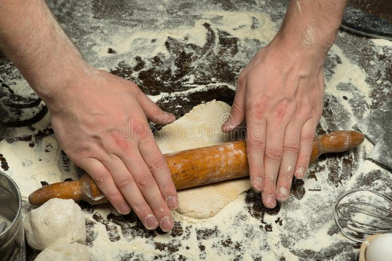 Las manos del cocinero están rodando una pasta fotografía de archivo