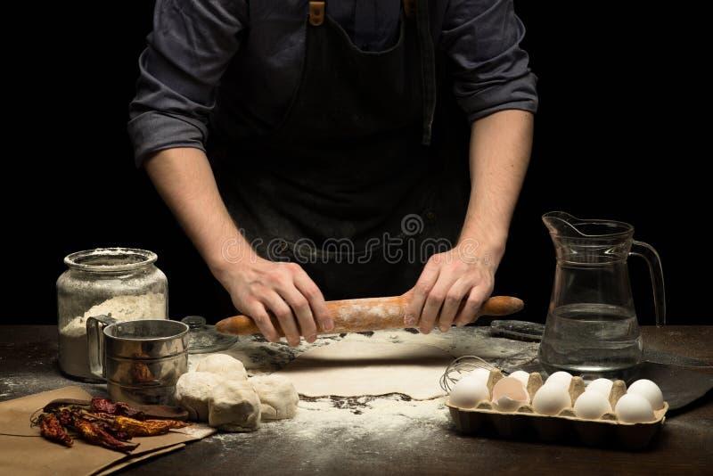 Las manos del cocinero están rodando una pasta para hacer la pizza imagen de archivo libre de regalías