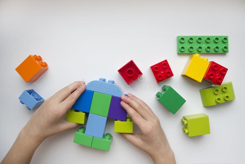 Las manos del constructor del colector del niño Juguetes educativos para los niños jovenes foto de archivo libre de regalías