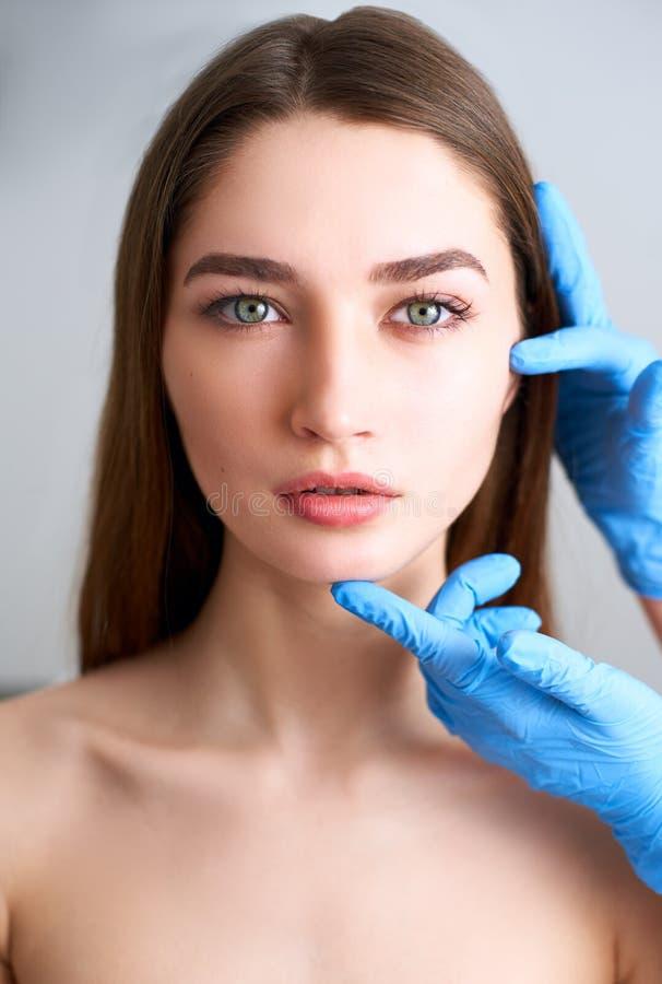 Las manos del doctor del cosmet?logo en los guantes que tocan la cara de la mujer atractiva Modelo rubio de la moda despu?s del t fotos de archivo