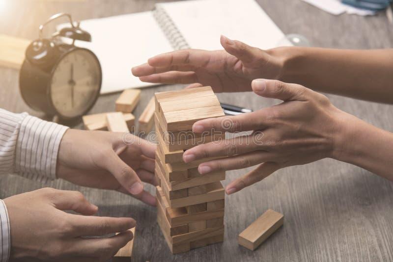 Las manos del ejecutivo cooperan poniendo el bloque de madera en la torre imagen de archivo
