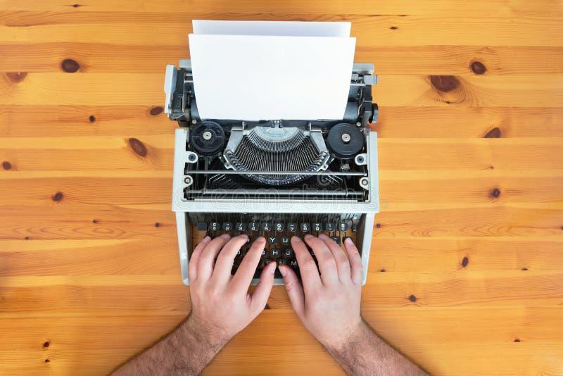 Las manos del escritor Máquina de escribir retra vieja en el escritorio de madera imagenes de archivo