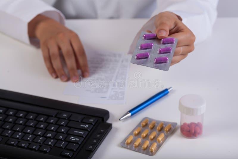 Las manos del farmacéutico durante realizar la prescripción fotos de archivo libres de regalías