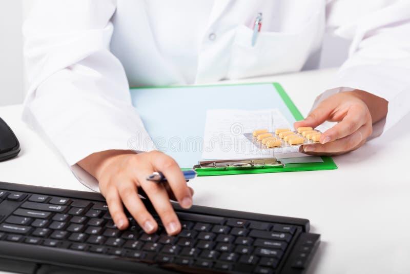 Las manos del farmacéutico que realizan la prescripción imagenes de archivo