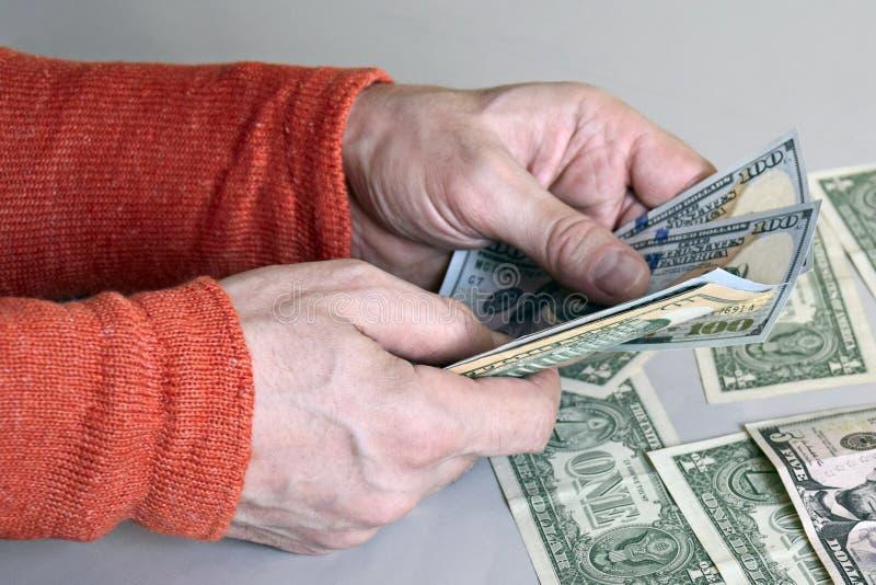 Las manos del hombre caucásico que cuentan billetes de banco del dólar imagen de archivo