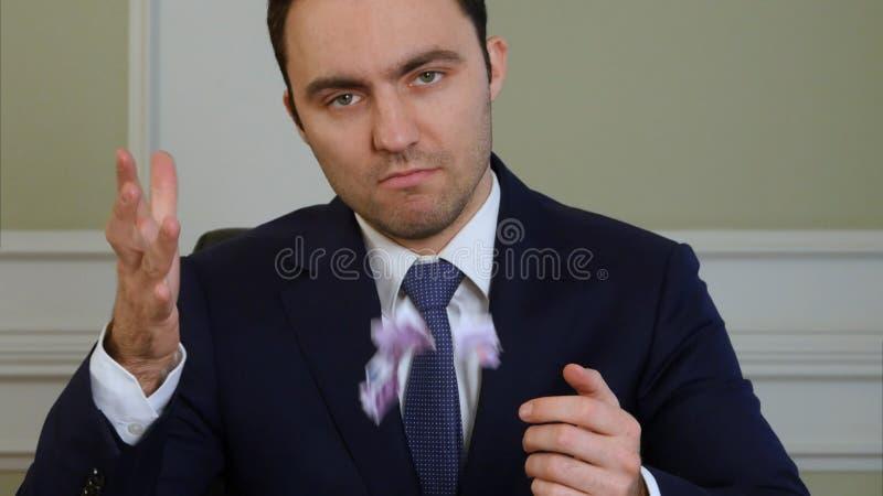 Las manos del hombre de negocios s rasgan el dinero y lo lanzan foto de archivo