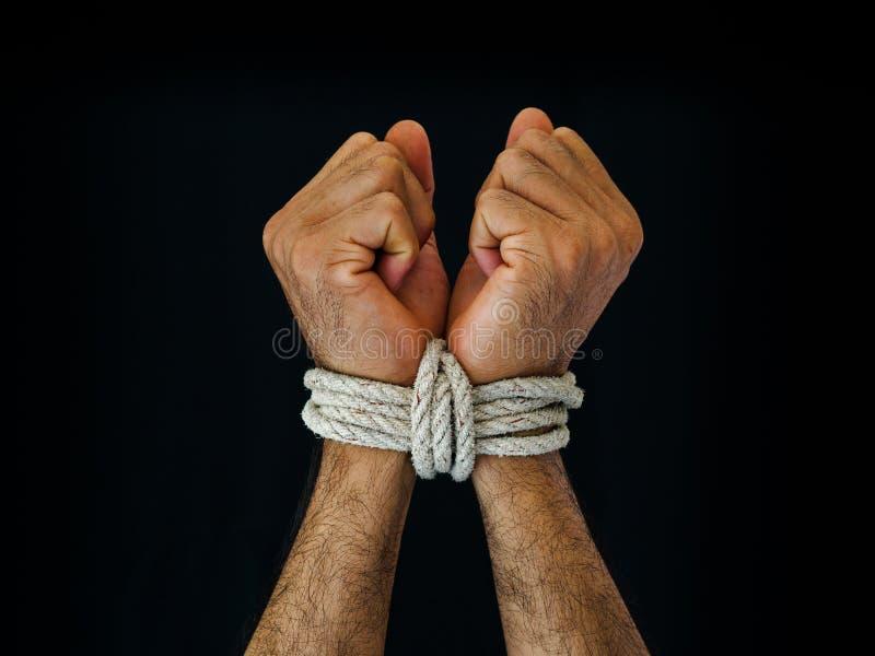 Las manos del hombre fueron atadas con una cuerda Violencia, aterrorizada, ser humano Righ foto de archivo
