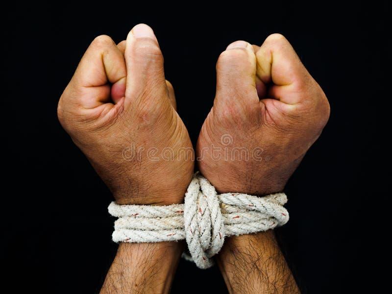 Las manos del hombre fueron atadas con una cuerda Violencia, aterrorizada, ser humano Righ fotos de archivo