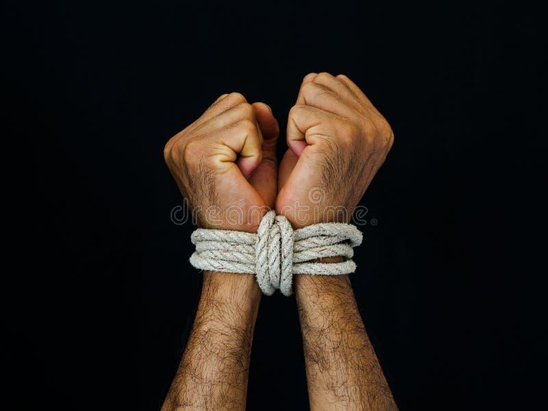 Las manos del hombre fueron atadas con una cuerda Violencia, aterrorizada, ser humano Righ imagenes de archivo