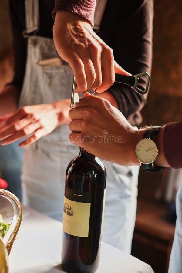 Las manos del hombre joven abren una botella de vino en un partido fotos de archivo