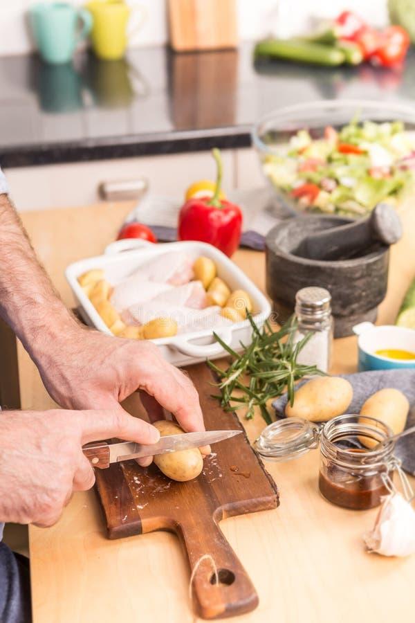 Las manos del hombre o del cocinero que preparan la cena en un plato de la asación imagen de archivo libre de regalías