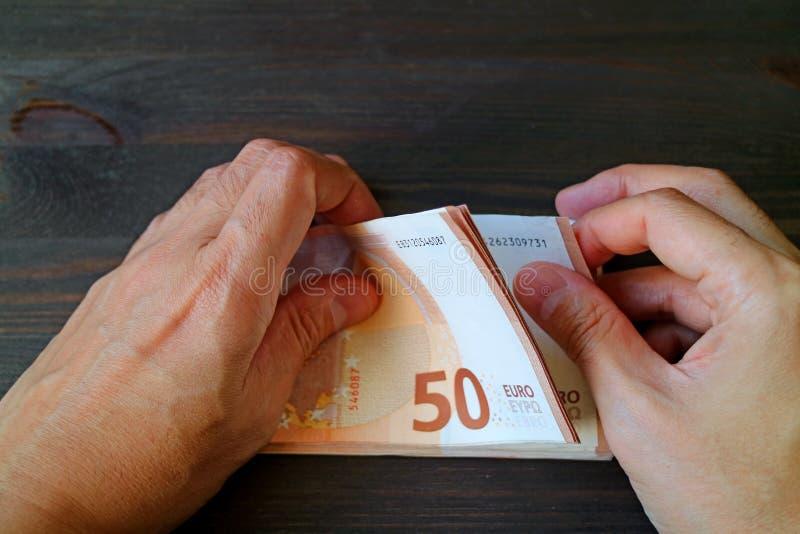 Las manos del hombre del primer que cuentan 50 billetes de banco EURO en la tabla de madera del color oscuro foto de archivo libre de regalías