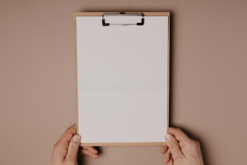 Las manos del hombre que llevan a cabo un tablero de clip en un fondo gris imagenes de archivo